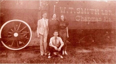 hank-williams-about-age-thirteen-joins-his-mother-lillie-his-sister-irene-and-his-cousin-j-c-mcneil-in-front-of-one-of-the-w-t-smith-log-trains